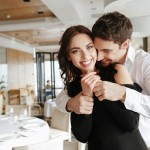 Photo of young loving happy couple hugging in restaurant indoors. Woman looking at camera.