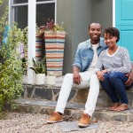 photodune-20641960-young-couple-sit-looking-to-camera-outside-their-new-house-xl