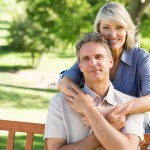 Portrait of loving woman embracing man from behind in park
